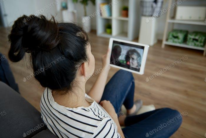 Rückansicht der Frau mit einer Video konferenz mit Großeltern.