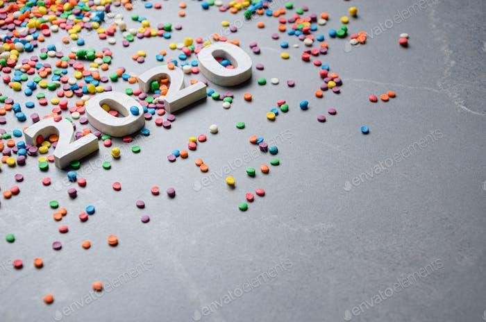 Números blancos 2020 con rociadores de azúcar de color en la mesa de piedra