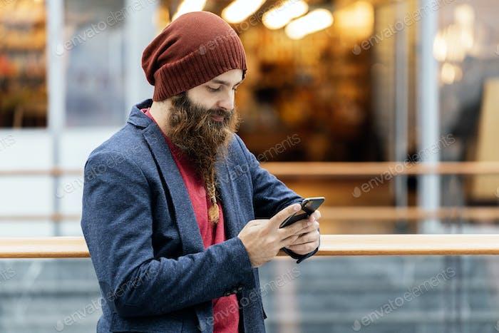 Stylish bearded man using phone indoors