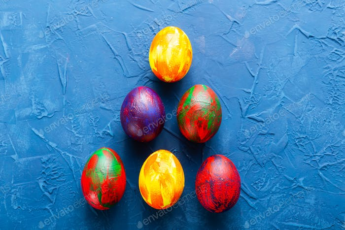 Multi-colored decorative colourful eggs on a blue background. Top view.