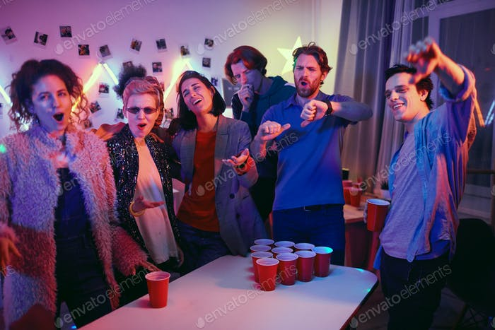 People playing in beer pong at home