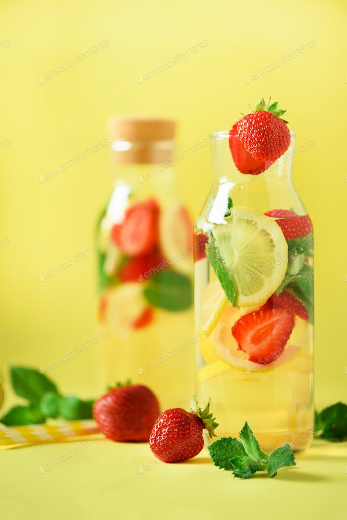 Fresh fruit flavored water with strawberry, lemon, mint on yellow background. Summer drink concept