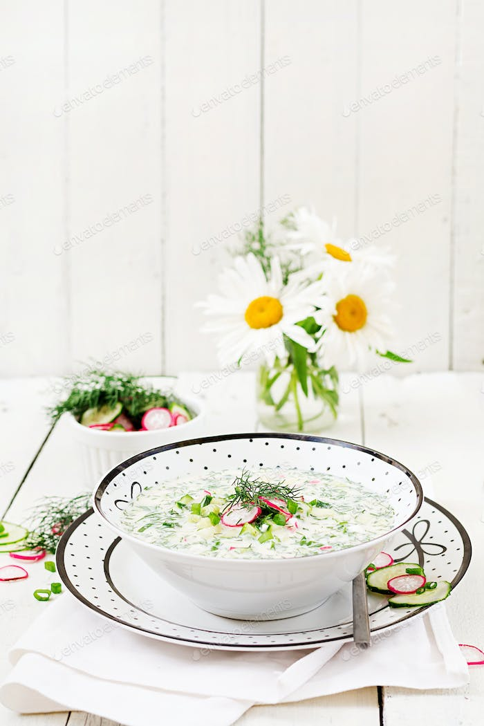 Cold soup with fresh cucumbers, radishes with yoghurt in bowl on wooden background.