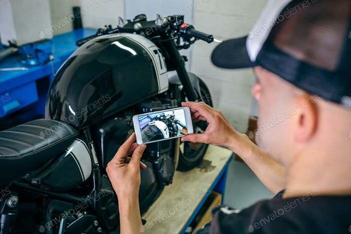 Mechanic taking picture of customized motorcycle