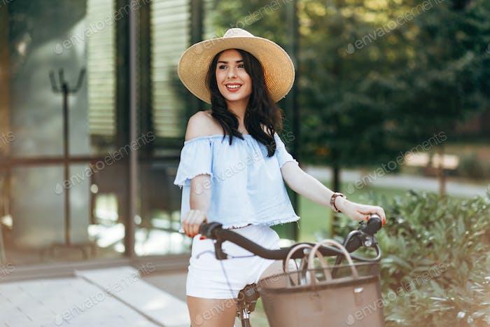 Красивая женщина с помощью велосипед