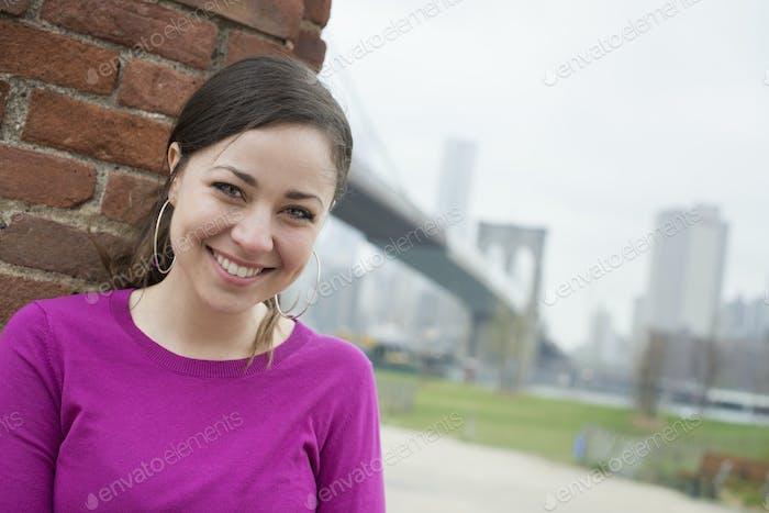 Mujer en la ciudad sentada apoyada contra una pared de ladrillo, revisando su teléfono inteligente.
