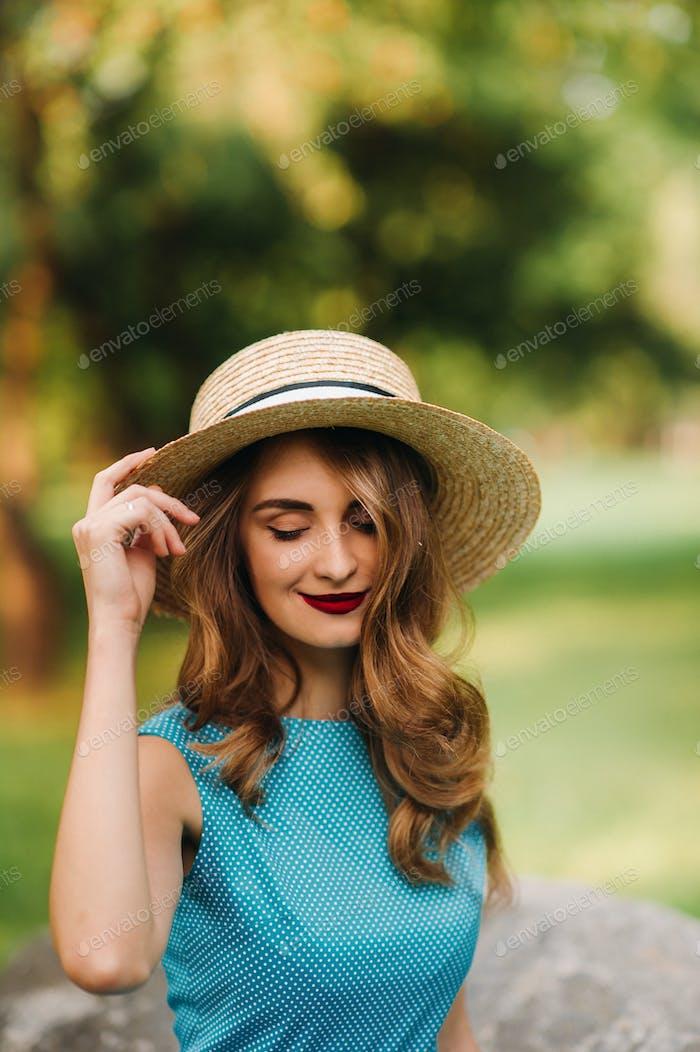 Портрет модной девушки в синем платье и элегантная шляпа в парке