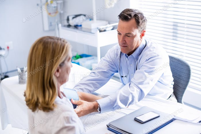 Doctor checking blood pressure of a patient in clinic