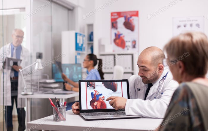 Young doctor pointing at heart on laptop screen