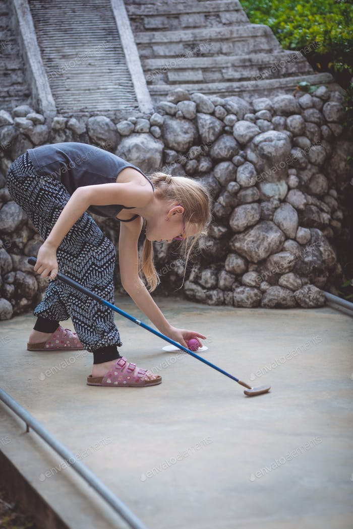 Happy little girl  playing mini golf.
