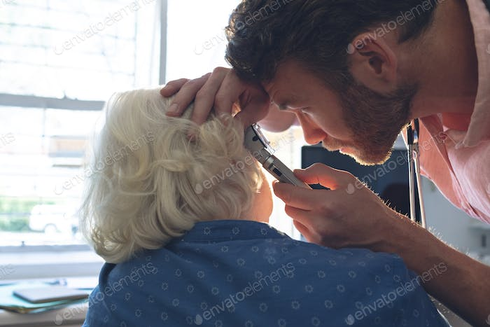Side view of Caucasian male doctor checking senior female patient ear with otoscope in clinic