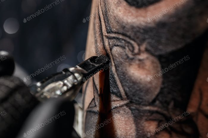 Artist tattooing of man's skin