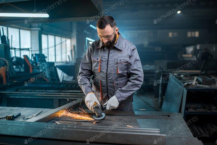 Metal industry worker at factory in work wear