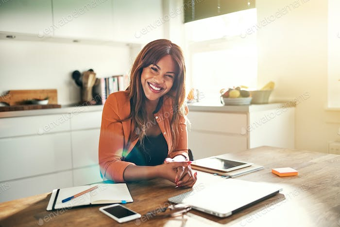 Smiling female entrepreneur talking on a cellphone in her kitchen