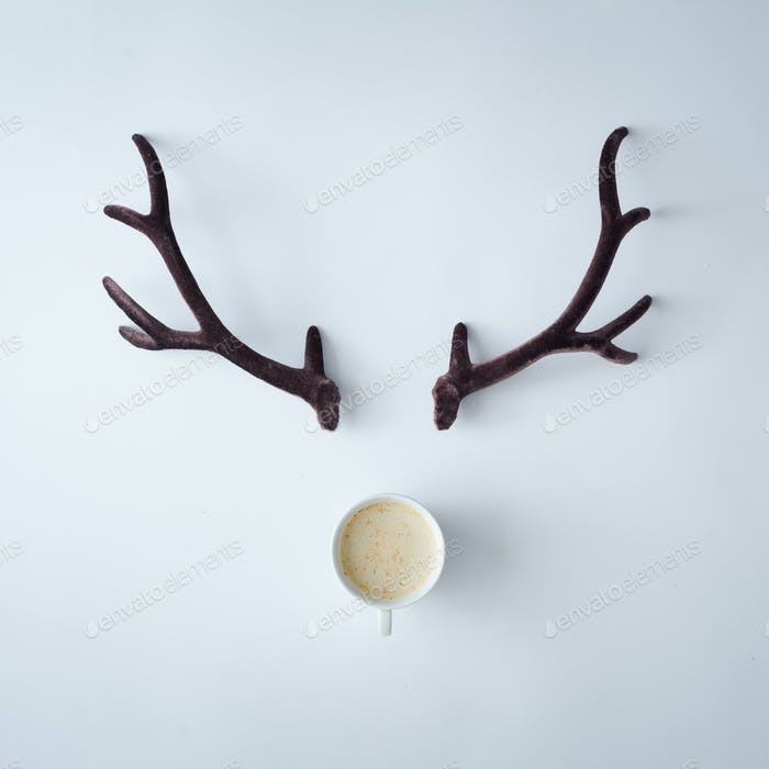 Christmas reindeer concept made of coffee cup and antlers on pastel grey background.