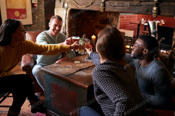 Group Of Friends Making Toast As They Meet For Lunchtime Drinks In Traditional English Pub