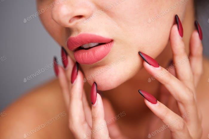 partial portrait of woman with red manicure and flawless complexion