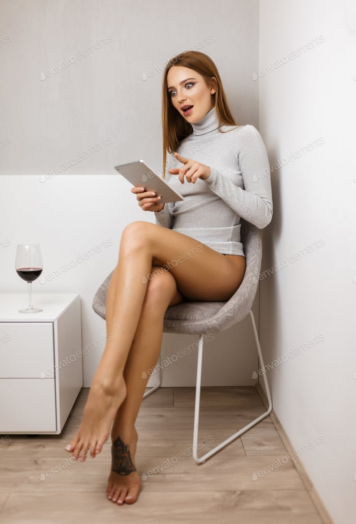 Pretty lady in sweater sitting and amazedly looking in tablet computer with glass of red wine near
