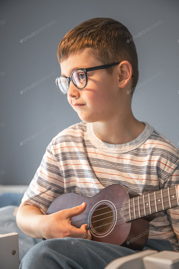Little boy playing ukulele sitting on the bed at home.