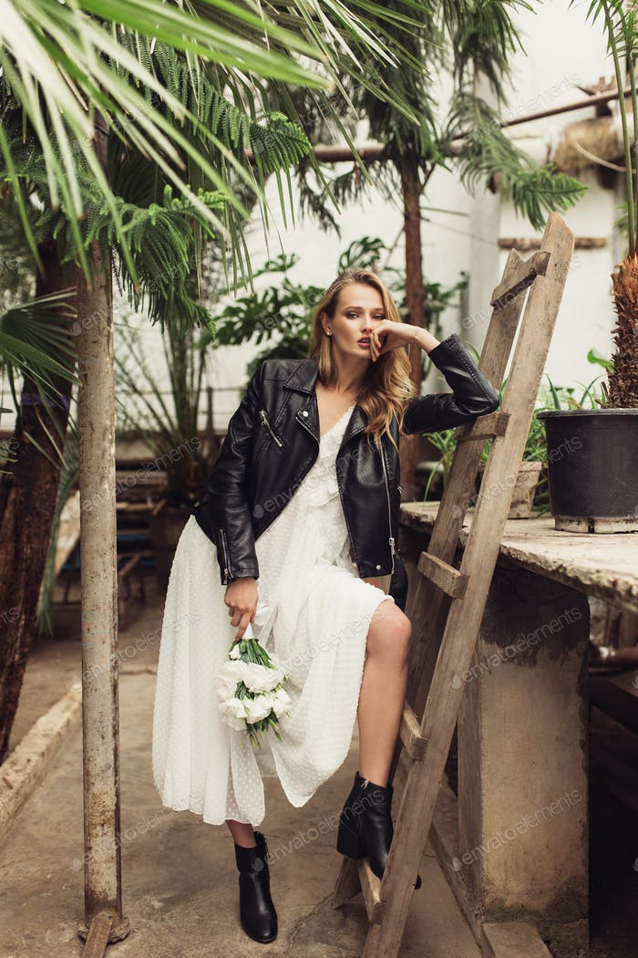 Young attractive woman in black leather jacket and white dress h