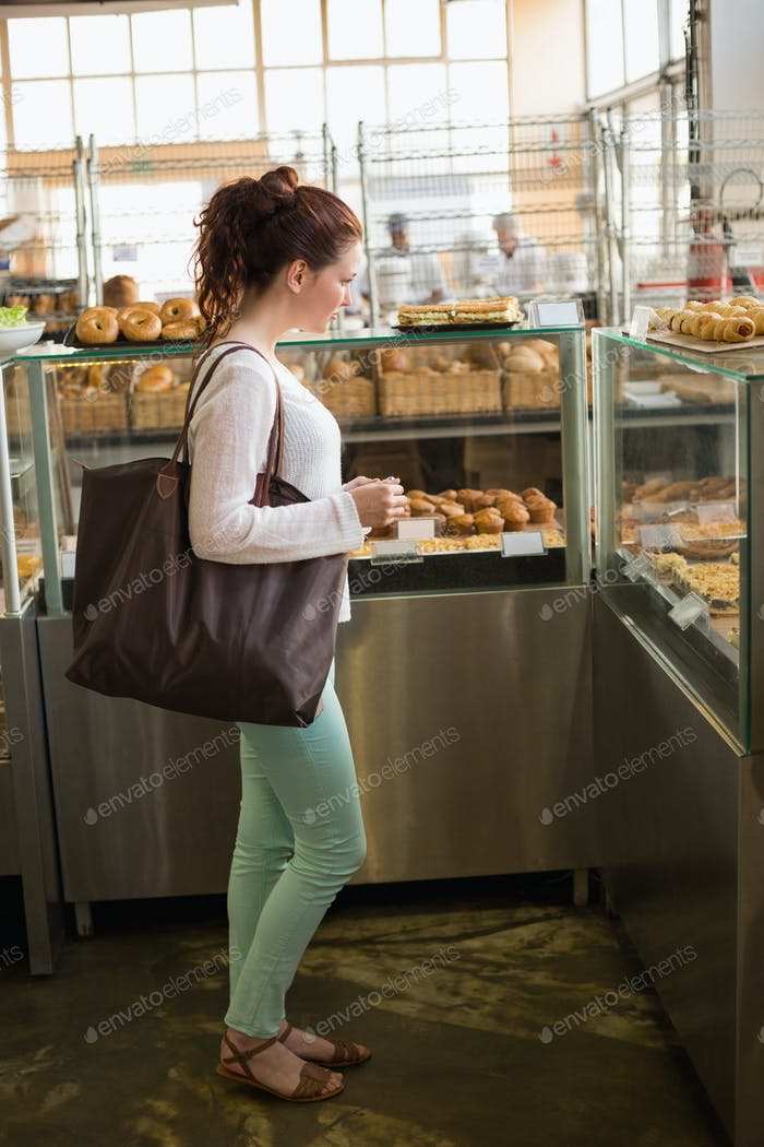 Pretty brunette shopping for bread at the bakery