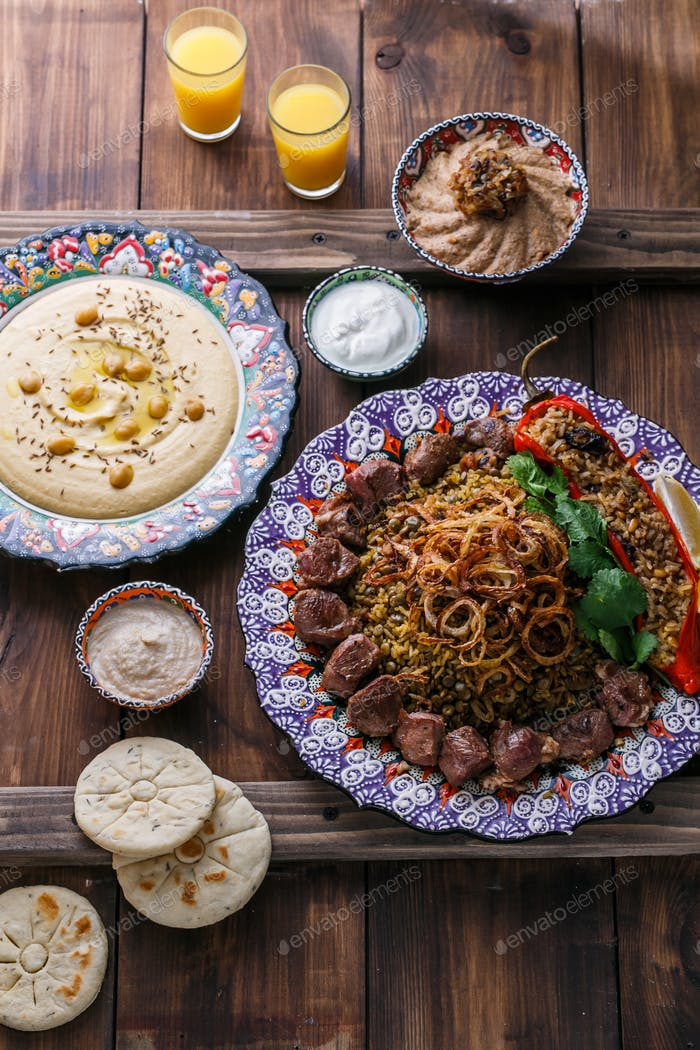 Mejadra with hummus, kashke bademjan and pitas, wooden background