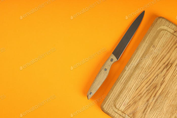 Cutting board with knife on orange background
