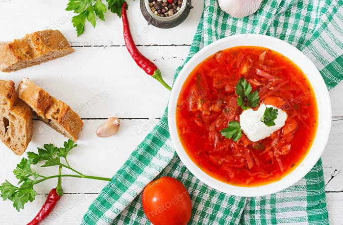 Traditional Ukrainian Russian vegetable borscht on the white wooden background. Top view