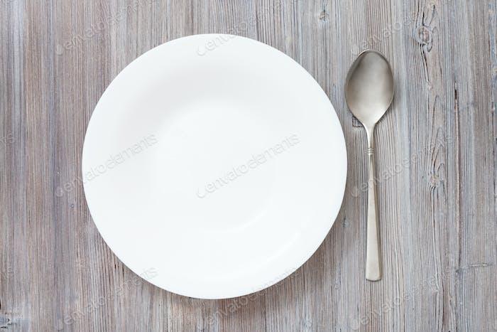 Draufsicht tiefer Teller und Löffel auf graubraunem Tisch