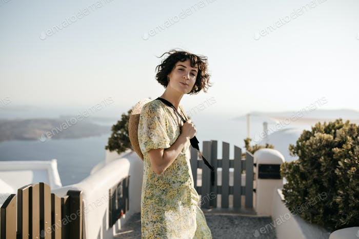 Short-haired brunette woman in summer dress looks into camera. Charming lady in floral dress smiles