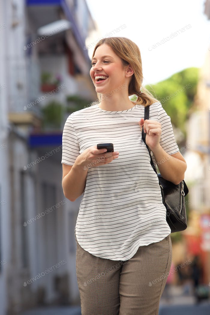 happy young woman walking in the city with mobile phone and bag