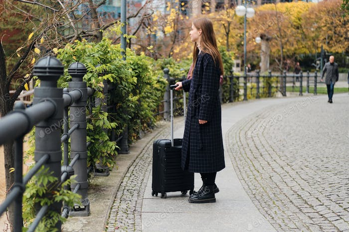 Side view of attractive casual girl in coat thoughtfully walking through street with black suitcase