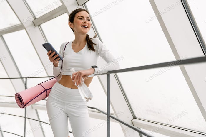 Brunette smiling sportswoman using mobile phone while leaning on railing