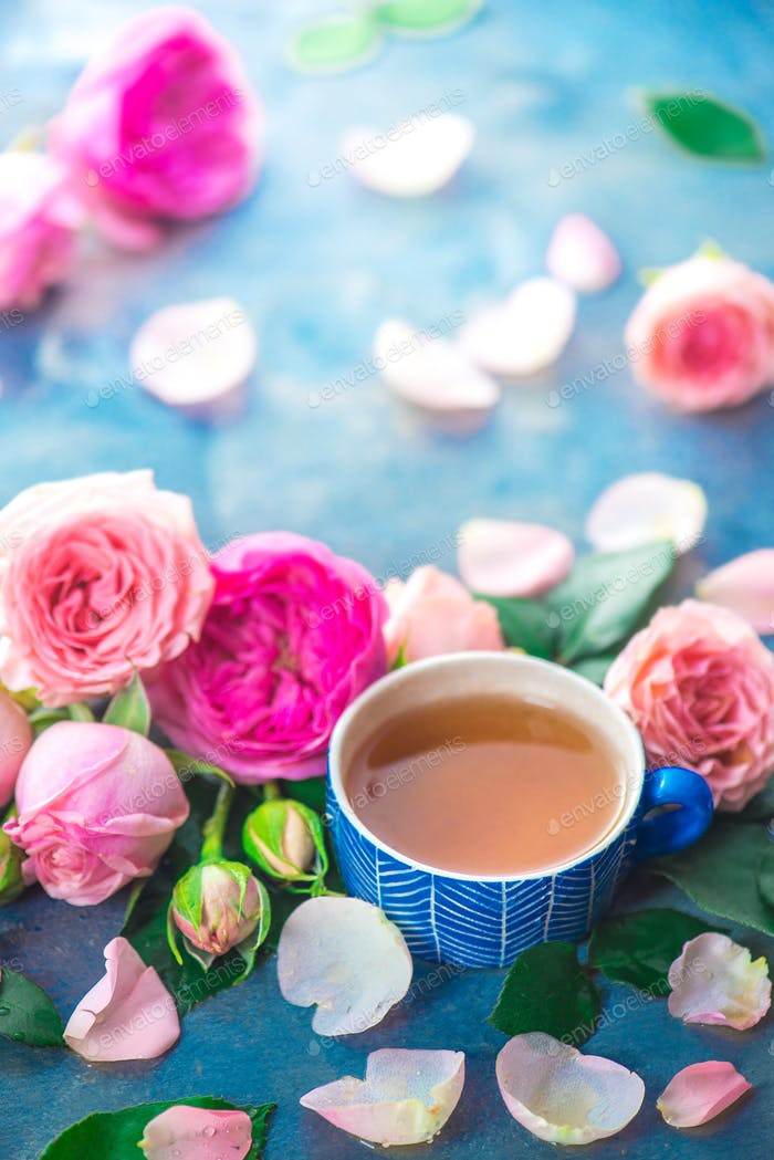 Rose tea in ceramic tea cups and flower petals on a wet light background with copy space. Seasonal
