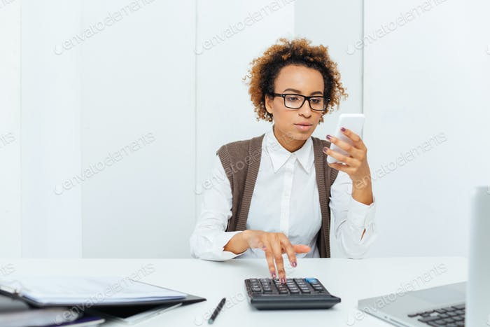 Thoughtful african woman accountant working with calculator and using smartphone