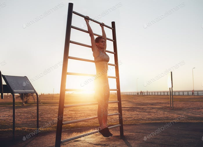 Fitness woman doing stretching workout on wall bars