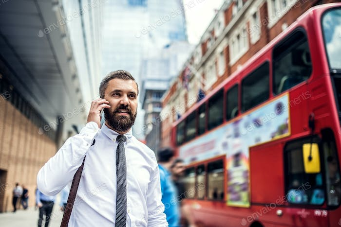 Hipster businessman on the street in London, making a phone call.