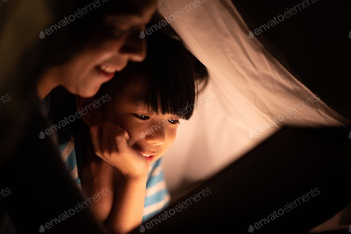 Happy mother and her little daughter reading book on the bed with cozy night and camping