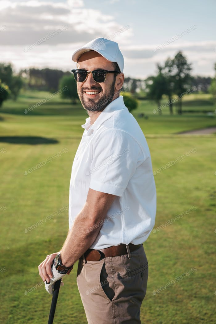 Handsome man in sunglasses holding golf club and smiling at camera