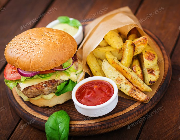 Big sandwich - hamburger with juicy beef burger, cheese, tomato,  and red onion on wooden background