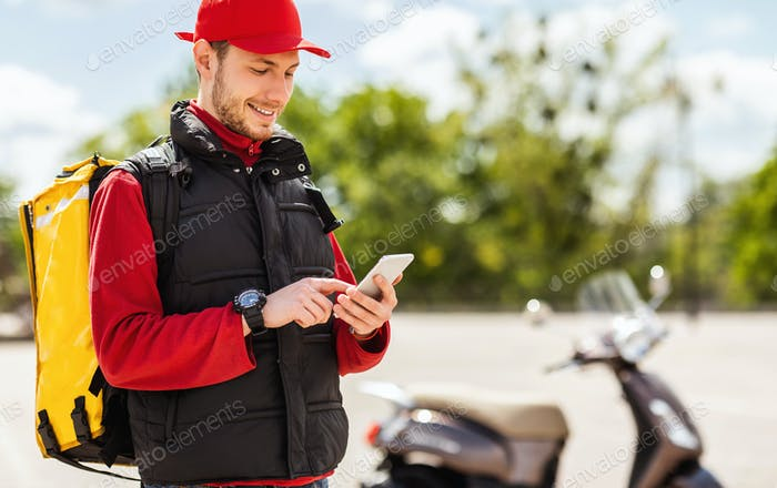 Delivery Man Using Smartphone Delivering Food On Scooter Standing Outdoor