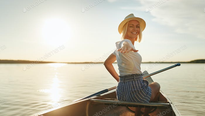 Smiling woman canoeing on a lake in the late afternoon