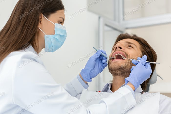 Man patient making check up in dental clinic