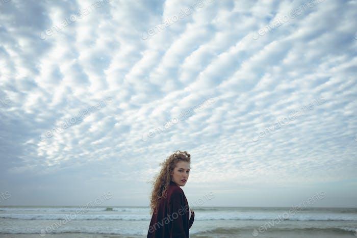 Женщина с вьющимися волосами глядя на камеры на пляже
