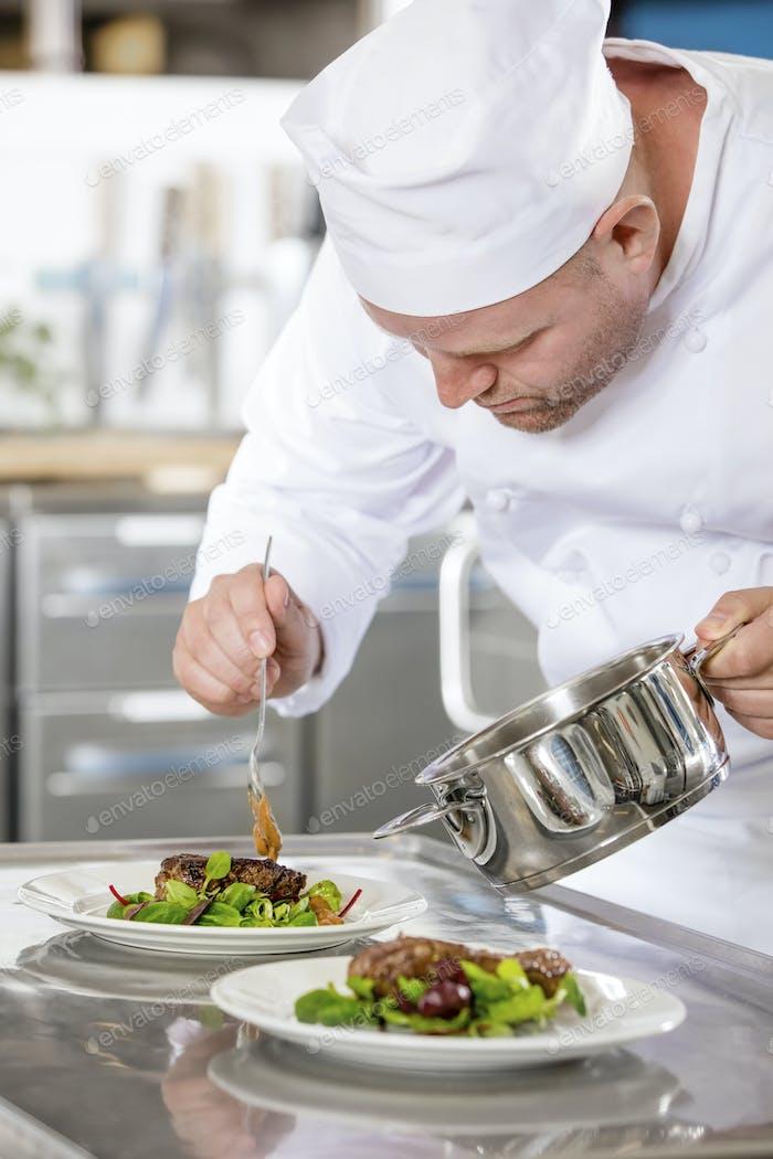 Focused professional chef prepare meat dish at restaurant