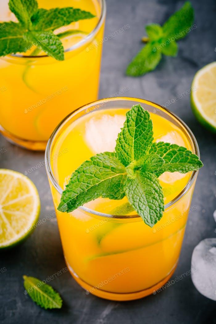 Frische sommerliche gelbe Limonade mit Limette und Minze