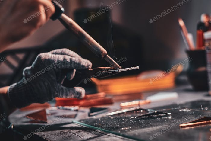 Process of soldering by hands at glass workshop