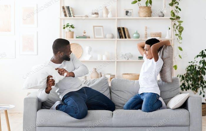 Happy Black Preteen Boy Genießen Kissen Kampf Mit seinem Vater Zu Hause