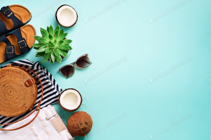 Female birkenstock sandals, jeans, striped t-shirt, rattan bag, coconut and sunglasses on blue