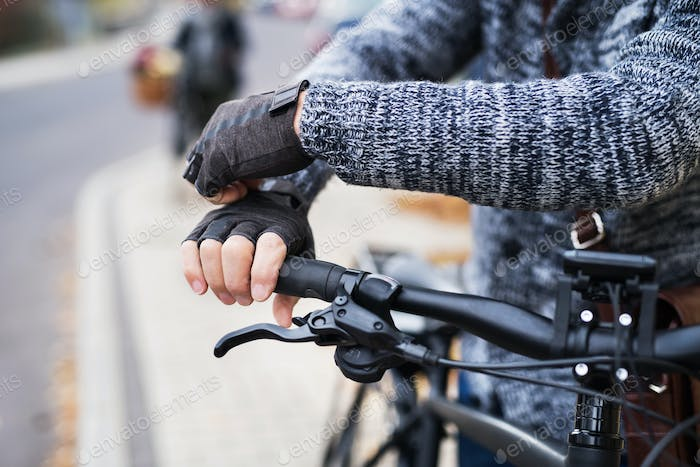 A close-up of a cyclist with electrobike putting on gloves outdoors in town.